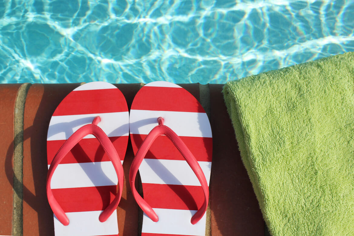 red and white flip flops by the pool